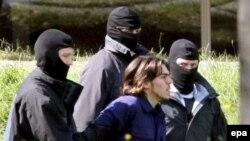 Один из подозреваемых по дороге в федеральный суд, который дал санкцию на арест «террористов»