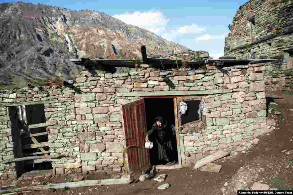 An old woman throws dirty water out of her house in Khyurdabakh, in the mountains of Daghestan. Patimat Musalmagomedova is the last permanent resident of the village.