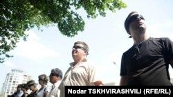 «Встаньте шире!» - с этими словами сотрудники «Алия Холдинга» выстроились перед зданием МВД в Тбилиси