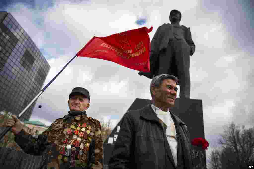 People hold flags and flowers as they arrive to pay tribute to Lenin by a statue in Donetsk, eastern Ukraine, on April 22, the 145th anniversary of his birth. (​AFP/Behrouz Mehri)