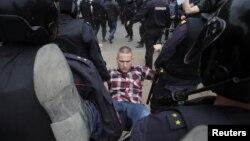 Полицейские несут задержанного на акции протеста в Петербурге. 12 июня 2017 года.