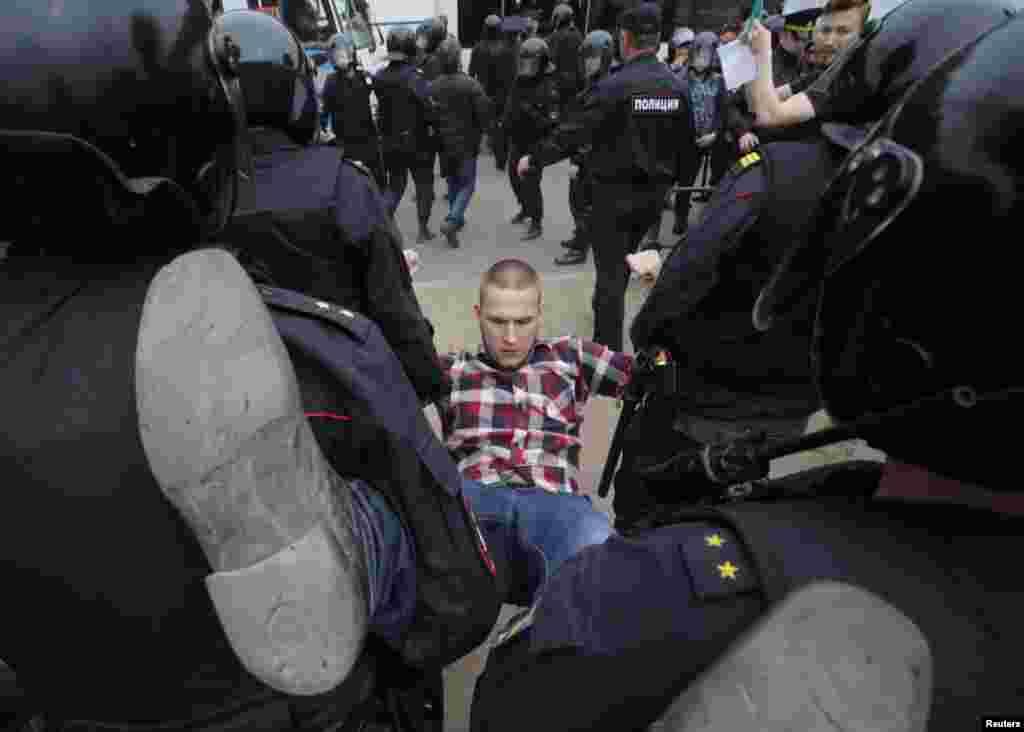 Полицейские тащат в автобус еще одного участника антикоррупционного митинга на Марсовом поле в Петербурге.