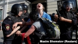 Police detain a young protester during an unsanctioned rally in Moscow on July 27.