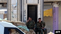 Soldiers man a checkpoint in the city of Rastan in central Homs Province.