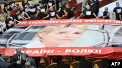 Opposition lawmakers roll out a giant poster featuring Yulia Tymoshenko in parliament in Kyiv on September 6.
