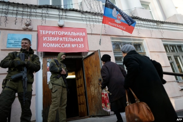 Two voters walk past pro-Russian rebels at a polling station in Donetsk.