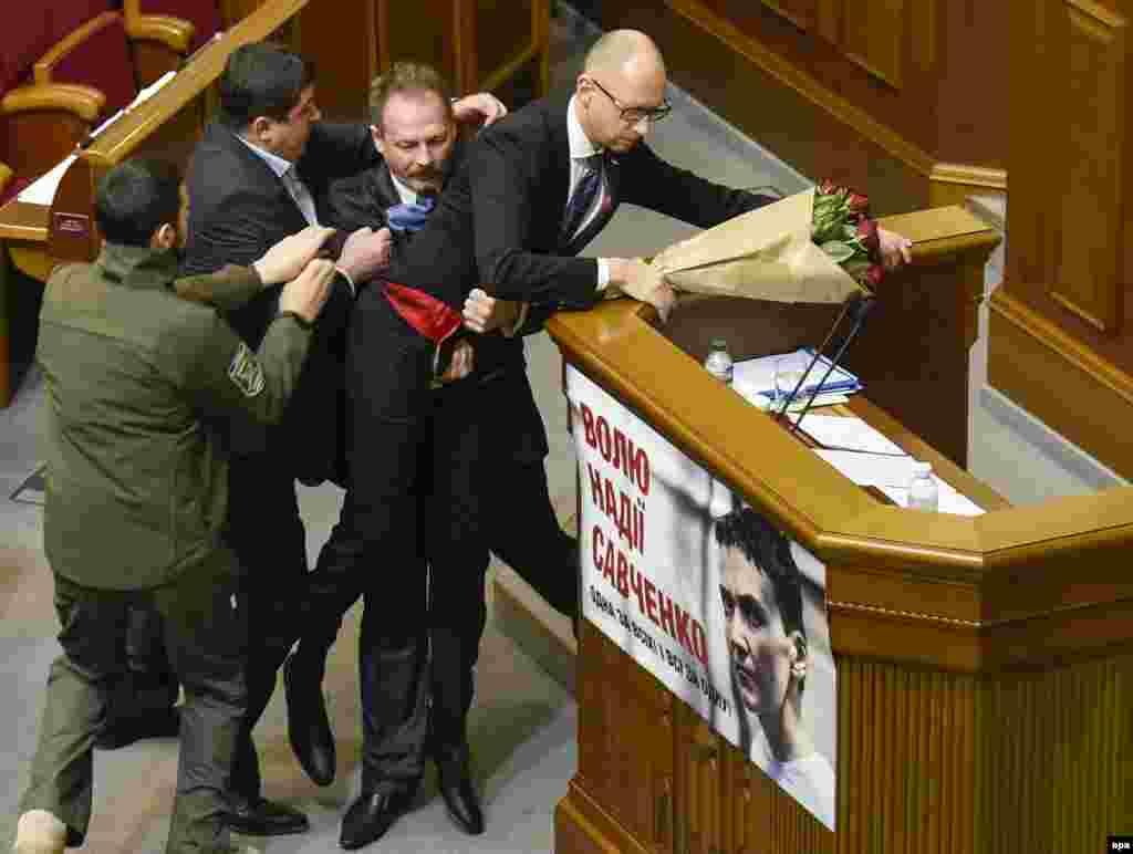 Ukrain parliamentiniň deputaty Oleh Barna (sagdan ikinji) premýer-ministri tribunadan aýyrjak bolýar. Kiýew, 11-nji dekabr. (epa/Aleksandr Kosarev)