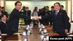 South Korea Unification Minister Cho Myung-gyon (left) shakes hands with North Korea's chief delegate, Ri Son Gwon during their meeting at the border truce village of Panmunjom in the Demilitarized Zone (DMZ) dividing the two Koreas on January 9.