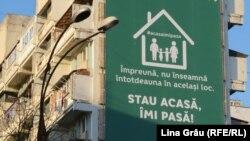 Panou publicitar cu îndemnul de a sta acasă pe un bloc din Chișinău