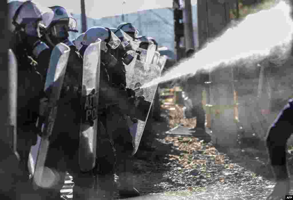 Грэцкая паліцыя разганяе мігрантаў, якія спрабуюць перайсьці грэцка-македонскую мяжу каля вёскі Ідамэні. (AFP/Armend Nimani)