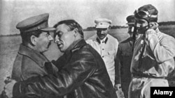Soviet dictator Josef Stalin looks unsure as pilot Valery Chkalov (right) leans in for a kiss in 1936.