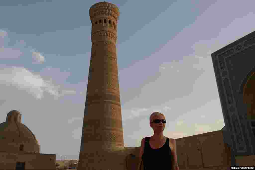 Sabina Fati in front of a tower in Buhara, Uzbekistan.