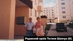 Тетяна Шевчук із сім'єю поряд із будинком, в якому їй надали службову квартиру, 2007 рік