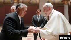 Pope Francis (right) shakes hands with Hungarian Prime Minister Viktor Orban at Romanesque Hall in the Museum of Fine Arts in Budapest on September 12.
