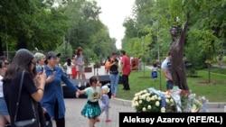 Памятник Денису Тену и цветы у его подножия, принесенные участниками торжественного открытия. Казахстан, Алматы, 22 июня 2019 года.