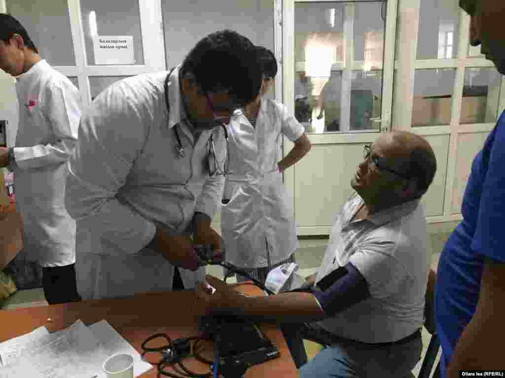 Доктор измеряет кровяное давление у человека, эвакуированного из города Арысь.