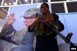 Афганский солдат стоит на фоне портрета вице-президента Афганистана Абдула Рашида Дустума. Герат, 30 августа 2015 года.