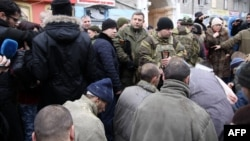 Captured Ukrainian soldiers kneel as the leader of the self-declared Donetsk People's Republic, Aleksandr Zakharchenko (center), stands and members of the media film at a bus stop where up to 13 civilians were killed.