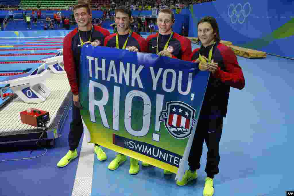 "The U.S. gold-medal-winning team of Nathan Adrian (left to right), Michael Phelps, Ryan Murphy, and Cody Miller pose with a banner saying ""Thank you Rio"" during the podium ceremony of the men's swimming 4 x 100-meter medley relay final."
