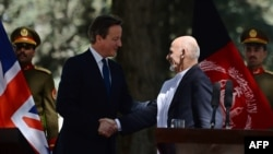 Afghan President Ashraf Ghani (R) shakes hands with British Prime Minister David Cameron (L) during a press conference at the Presidential palace in Kabul, October 3, 2014.