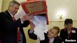 Members of a local election committee emptied a ballot box after polls closed in Minsk in the country's last election, the December 19 presidential vote that sparked protests and a brutal crackdown.