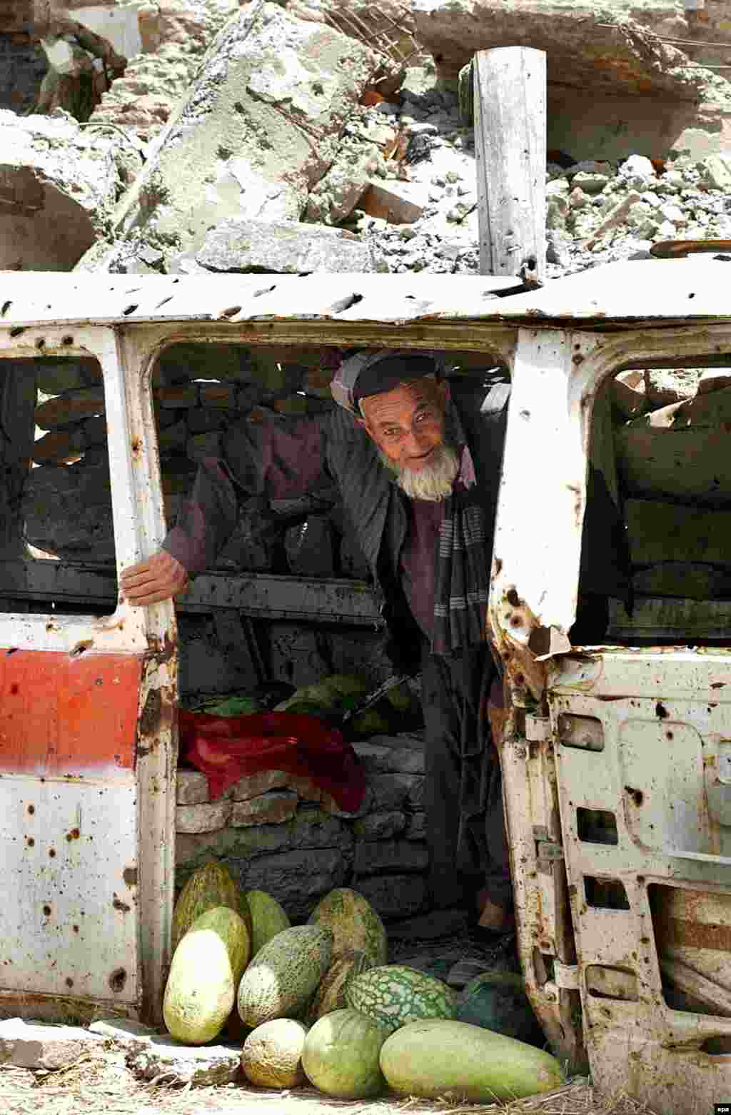 An elderly fruit vendor sets up shop inside a bullet-riddled car in Kabul (epa) - The government raises pitifully little in taxes. Yet it faces a reconstruction effort of huge proportions. Inevitably, Afghanistan is critically dependent on foreign aid to develop, and roughly one in 10 Afghans still requires food aid to subsist.