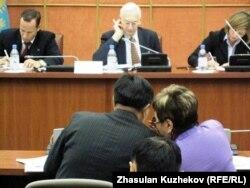 Жақып Асанов пен Айгүл Соловьева (бергі қатарда) сыбырласып отыр. Астана, 14 желтоқсан 2010 жыл.