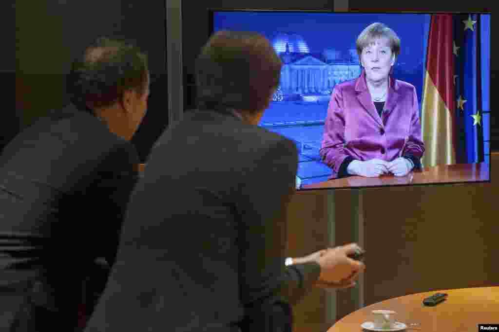 مردم در حال تماشای سخنرانی آنگلا مرکل به مناسبت سال نوی میلادی در آلمان