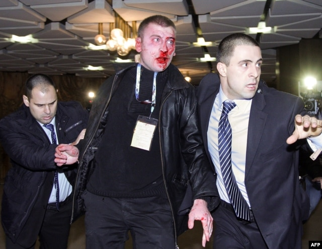 A bloodied Oktay Enimehmedov is led away from the scene of the attack by security personnel.