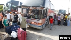 People unload their belongings in Baghdad from a bus that had traveled from Syria on July 20.