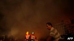 Палестинские пожарные на месте загоревшего завода после авиаудара израильских военных. 10 августа 2014 года.