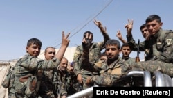"Fighters of the Syrian Democratic Forces make a ""V"" sign as they ride to the front-line in Raqqa on October 8."