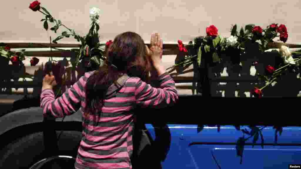 A woman kisses one of the three trucks carrying the coffins in front of the presidential building in Sarajevo on July 9.