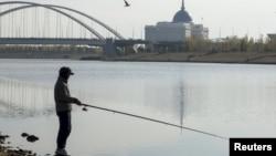 Мужчина ловит рыбу в Ишиме. На заднем плане — резиденция президента Казахстана. Астана, 12 октября 2015 года.