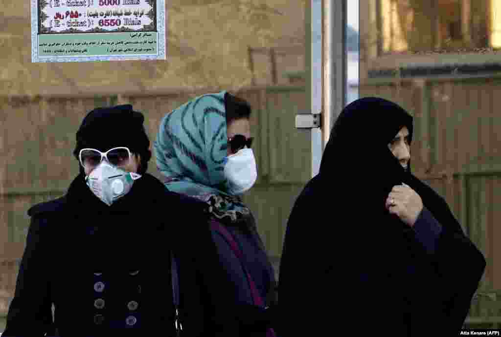 Iranian women wearing face masks wait at a bus stop as winter's heavy pollution hits new highs in the capital Tehran. (AFP/Atta Kenare)