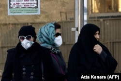 Iranian women wearing face masks wait at a bus stop in Tehran, which has long been plagued by a pollution problem. (file photo)