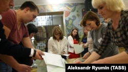 Members of a local election commission count ballots at a polling station following municipal elections in Ryzazan, Russia