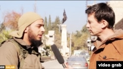 A screen shot from a video showing a French Islamic State militant (left) talking to British hostage John Candlie