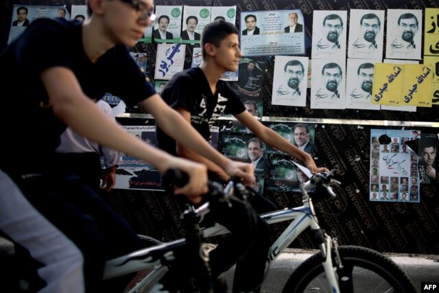 Iranian youth ride their bicycles past campaign posters in Tehran.