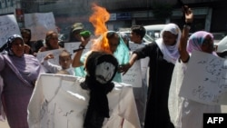 Rights activists torch an effigy of a Taliban member during a protest in Karachi on April 6 against the public flogging of a veiled woman.