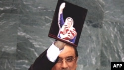 Asif Ali Zardari holds a photo of his slain wife as he speaks at the UN.