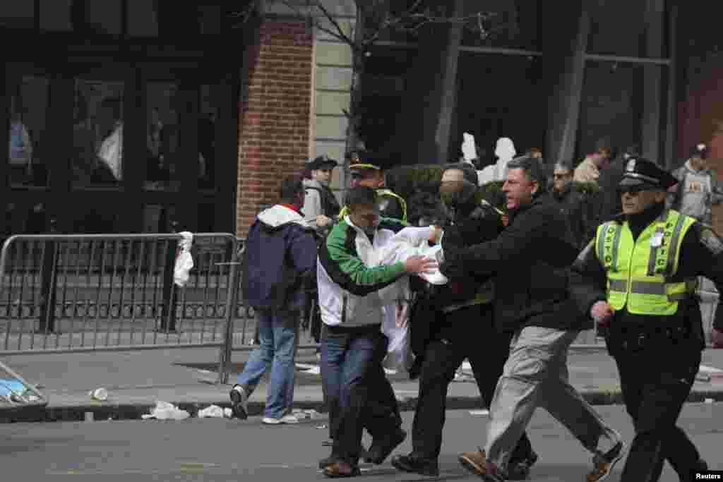 Люди забирають із місця вибуху пораненого