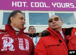 Russian President Vladimir Putin (right) and then-Sports Minister Vitaly Mutko attend a men's cross-country relay event at the 2014 Sochi Winter Olympics in February 2014.