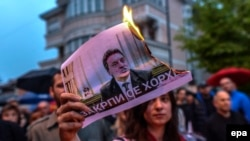 A protestor burns a picture of Macedonia's former Prime Minister Nikola Gruevski. The Balkan country has been in political turmoil since February 2015 over a wiretapping scandal.