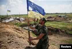 Український військовослужбовець тримає понівечений кулями прапор України на позиції біля міста Мар'їнка. Червень 2015 року