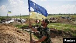Një pjesëtar i ushtrisë së Ukrainës duke e mbajtur flamurin e dëmtuar në një pozicion në pjesën lindore të Ukrainës