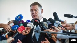 Romanian President Klaus Iohannis speaks to reporters after casting his ballot at a polling station in Bucharest on November 10.