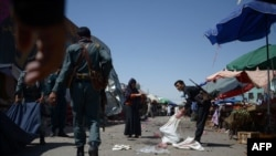 Afghan policemen investigate at the site of an attack after a suicide bomber blew himself up at a crowded marketplace in Mazar-e Sharif on August 9.