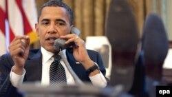 АҚШ президенті Барак Обама стол үстіне аяқтарын қойып, телефонмен сөйлесіп отыр. Вашингтон, 8 маусым 2009 жыл.