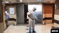 FILE: Health workers disinfect a building in Iran to prevent the spread of coronavirus.